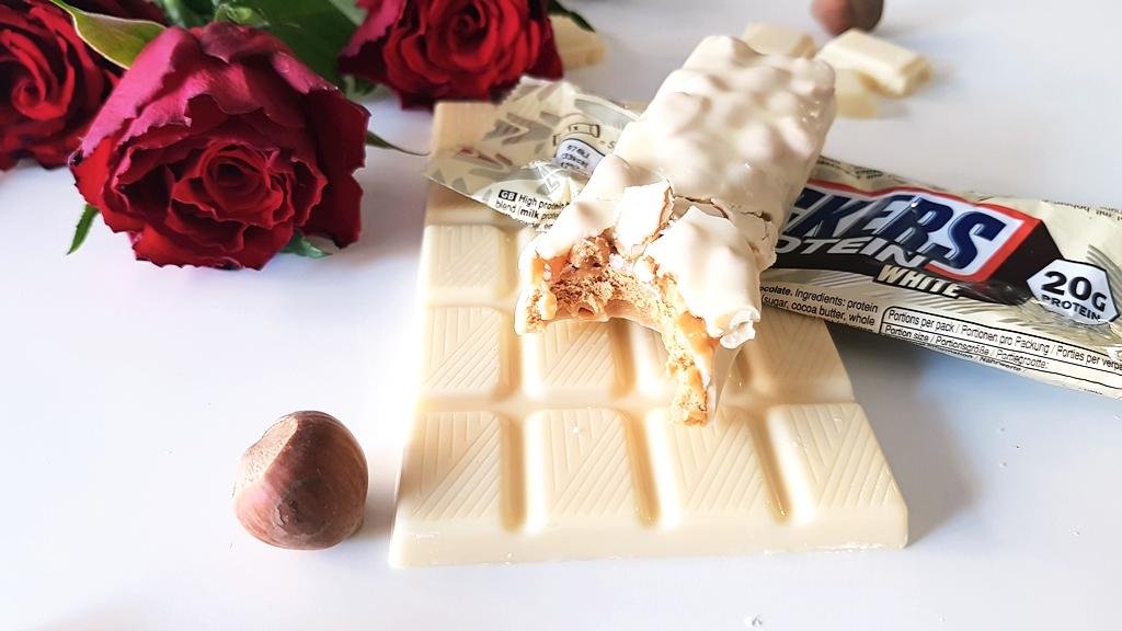 Snickers Hi Protein White, orzechy laskowe, róże i biała czekolada Milka